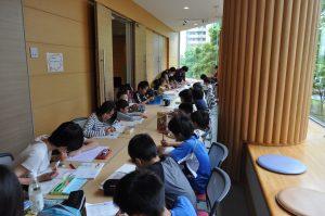 講堂前のスペースに机を並べて勉強する子供たち